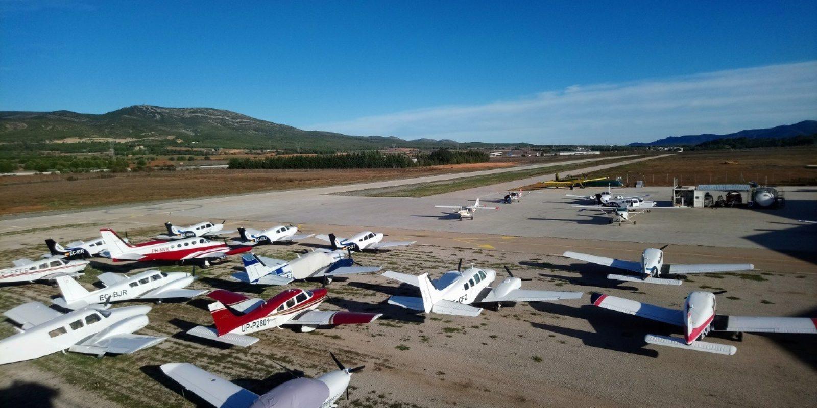 Een rijtje GA-toestellen broederlijk naast elkaar op het vliegveld van Requena - El Rebollar (LERE). Op de achtergrond het geelgeschilderde blusvliegtuig van het lokale brandweerkorps. (Foto Thomas Cruysberghs)